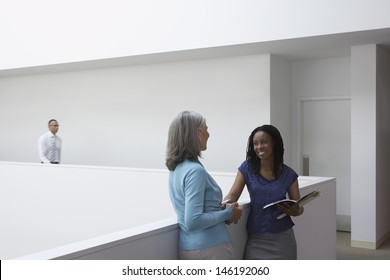 Businesswomen talking in office hallway with male colleague in background