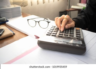 Businesswomen use calculator to calculate the monthly balance on the office desk.