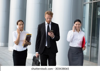 Businesswomen using cell phones while walking on path outside office. Man in black busines suit with brief case going to call to his secretary.