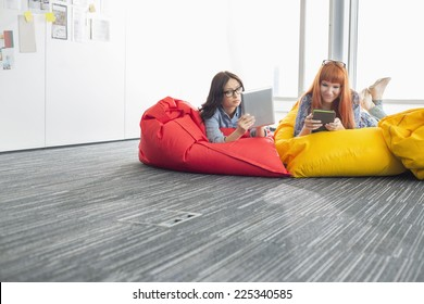 Businesswomen using digital tablets while relaxing on beanbag chairs in creative office