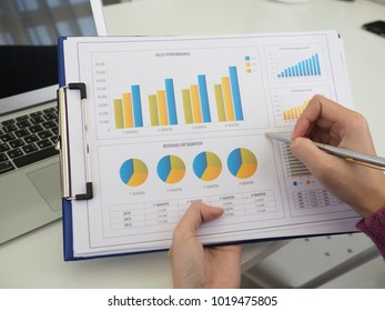 businesswomen using laptop analyzing marketing strategy with statistic graph and notebook on the table.