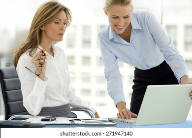 Businesswomen working together. One woman is using a laptop for presentation purpose, the other is listening.
