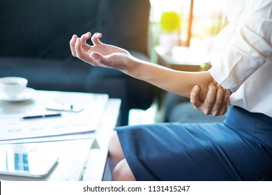 Businesswomen's elbow pain, A young woman touching her painful elbow