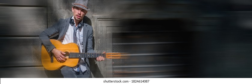 A busker street musician with guitar. Copy space.