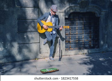 A busker street musician playing music with guitar on a city sidewalk.