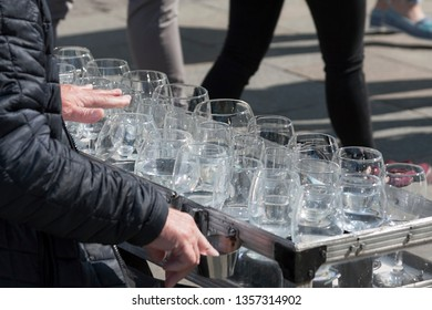 A busker, street performer, musician playing an unusual uncommon instrument made from wine glasses - glass harp. Concept of free street art performance and busking