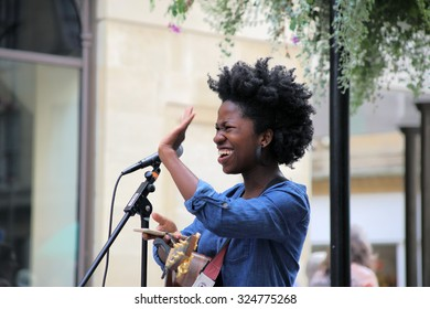 Busker in the Union street, Bath, England, 08.29.2015 A picture of a street singer and guitar player young lady, named Bee, who was singing in a public place, when the photo was taken.