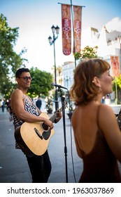 Buskers playing on a busy street in Seville, Spain. Guitarist man and singer woman. Latino guitarrist