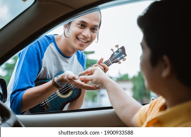 buskers receive by hand when someone gives coins from the car on the roadside