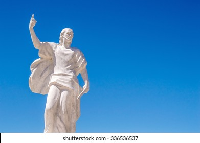 Busko Blato, Bosnia and Herzegovina - July 2015 - A stone statue of prophet Elijah holding a knife or a sword and pointing to the Heavens, with bright blue sky in the background