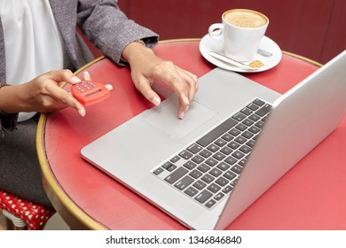 busniesswoman using e-banking token with laptop inside cafe