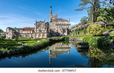 BUSSACO, PORTUGAL - 27 APRIL 2014: A panorama showing the facade and gardens of the luxury hotel at Bussaco Palace near Luso in Portugal reflected in a pond on a sunny summer's day.