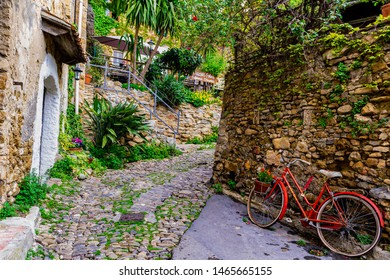 BUSSANA VECCHIA, IMPERIA, LIGURIA, ITALY - April 15, 2018: View of a red bicycle in the alley of the old village uninhabited after the earthquake of 1887.