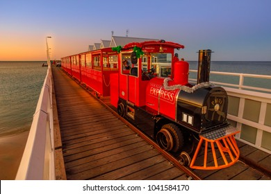 Busselton, Australia - Dec 30, 2017: Busselton Jetty Train on the longest wooden pier tracks in the world stretching almost 2 km out to sea. Scenic iconic famous place in Western Australia at twilight