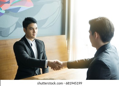 Bussiness done deal! Two modern asian bussinessman are shaking hands and smile while their meeting.