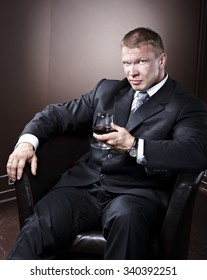Bussiness man boss sitting and smiling with a glass of wine
