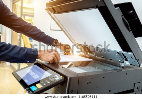 Bussiness man Hand press button on panel of printer, printer scanner laser office copy machine supplies start concept.