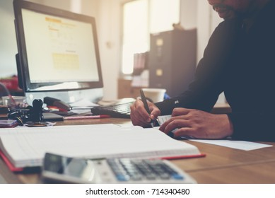 Bussiness man writing a payment check at the table and working on documents in the office,business concept