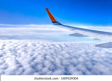 Bussiness and travel concept. Aerial view through window inside aircraft cabin with beautiful blue sky and cloud with sunlight, copy space, top view