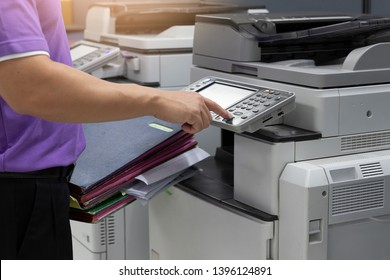 Bussinessman using copier machine to copy heap of paperwork in office.