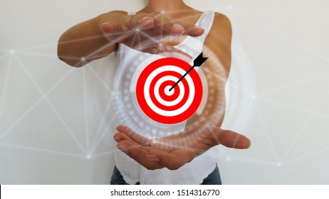 Bussinesswoman holding in hands target and arrow with digital interface - Shutterstock ID 1514316770