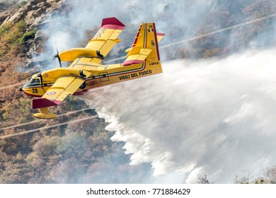BUSSOLENO, SUSA, TURIN -  October 23, 2017. Bombardier CL-415 Superscooper, Canadair 7 reg. I-DPCD, from Genoa and Rome Airport, launching water on fire during firefighting operation in Italy.