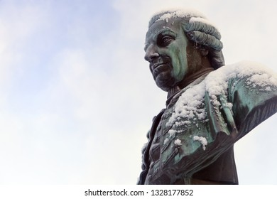 Bust of a man from the 1700s looking to the side and has now on him.