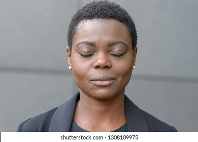 Bust portrait of black woman with short haircut and her eyes closed. Standing outside against grey wall in black jacket