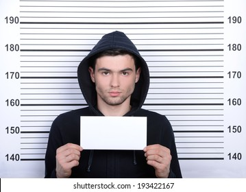 Busted burglar. Angry burglar holding a white poster while standing against police line-up