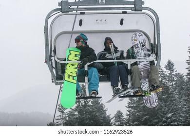 BUSTENI, ROMANIA, February 02, 2010: Three skiers are on ski lift to peak of Busteni mountain.
