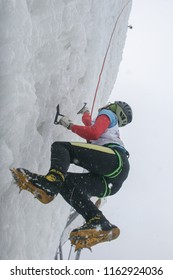 BUSTENI, ROMANIA, February 02, 2010: An ice climber on a frozen wall at competition in Busteni.