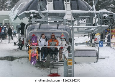 BUSTENI, ROMANIA, February 02, 2010: Group of people sitting on a ski lift to go peak of Busteni mountain.