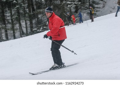 BUSTENI, ROMANIA, February 02, 2010: Red jajket man is skiing in  Busteni mountain with a smile in his face.