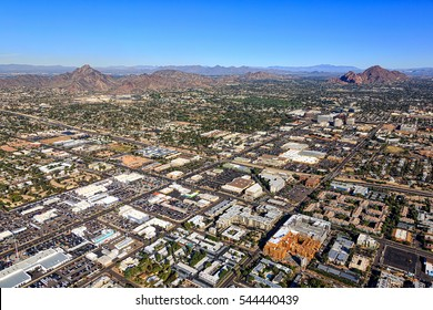 Bustling landscape along the Camelback corridor with aerial views of Piestewa Peak and Camelback Mountain looking northeast from uptown Phoenix, Arizona