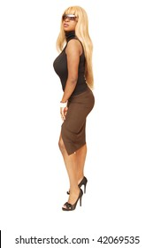 An busty young Jamaican woman in a black top and brown skirt with long  blond hair standing in a studio for white background.