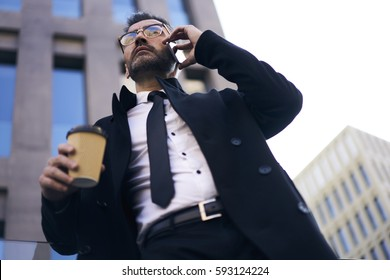 Busy administrative manager of business enterprise starting working day early in morning talking on phone with executive while hurrying for conference walking on city streets of financial district