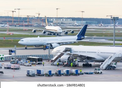 Busy airfield view with airplanes and service vehicles. View of International Airport with planes, gangways, trucks and service equipment. Travel and industry concepts