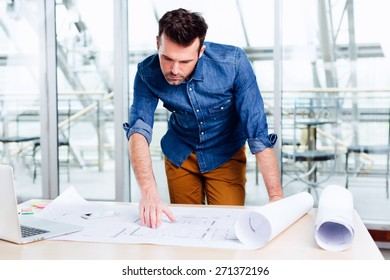 Busy architect checking the details of a blueprint