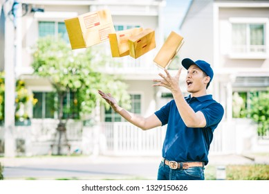 Busy Asian delivery man throw package boxes in the air outdoor