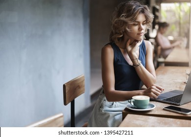 Busy attractive young modern businesswoman prepare project reading article sit near window cafe table drink coffee thinking look laptop display. Female student tutor make arrangements future lesson
