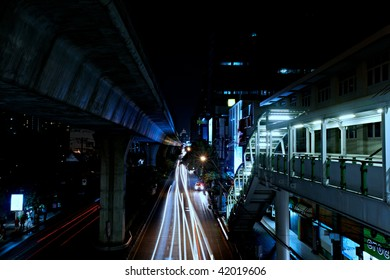 Busy Bangkok street at night with car motion blur.