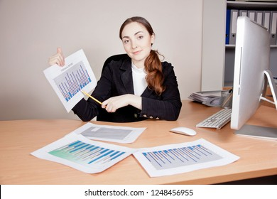 Busy beautiful businesswoman with financial report at office