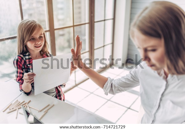 I'm busy! Beautiful young woman is working at home with her little cute daughter nearby. Don't have enough time for child.
