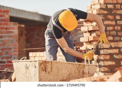Es ist voll mit Ziegelmauer. Bauarbeiter in Uniform- und Sicherheitsausrüstung haben eine Baustelle.