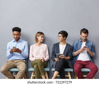 Busy business people, wait for meeting with boss: two guys chattes over cell phone or surf social networks and women have pleasant conversation, make acquintance, find common topic to discuss