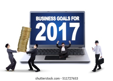 Busy business team and big notebook with text of business goals for 2017 on the monitor, isolated on white background