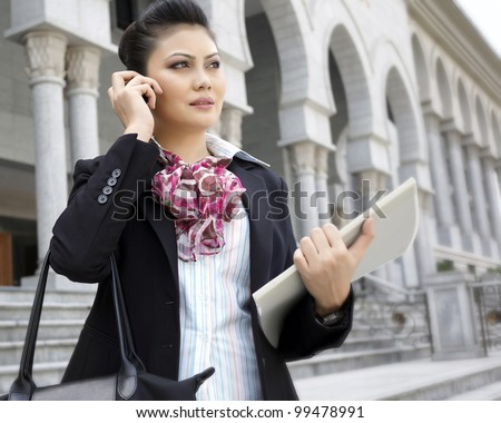 Busy business woman talking on phone while holding files