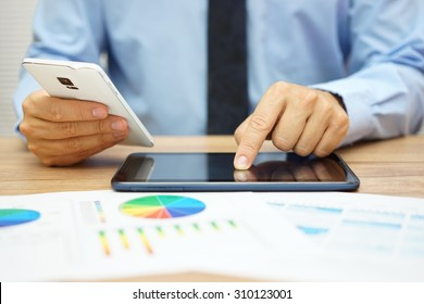 busy businessman  with financial documents working in office with tablet computer and smart phone at the same time