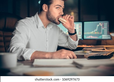 Busy businessman having late lunch eating sandwich in office working at night, stock broker trading online and eating snack looking at computer, workplace meal, overwork and food delivery concept