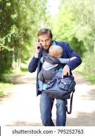 busy businessman with his son in a sling talks on the smartphone and try to opens up a backpack with documents, front view